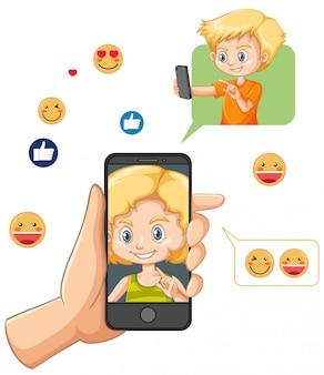 Hand, die smartphone mit emoji-symbol der sozialen medien lokalisiert auf weißem hintergrund hält