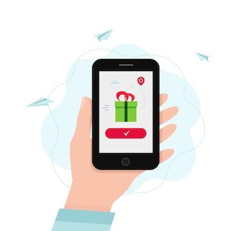 Hand, die smartphone mit geschenkbox auf einem bildschirm hält.