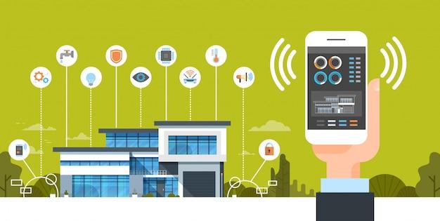 Hand, die smartphone mit intelligenter hauptsystemsteuerungsschnittstelle-modernem haus-automatisierungs-konzept hält