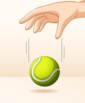 Hand, die tennisball für schwerkraftexperiment fallen lässt