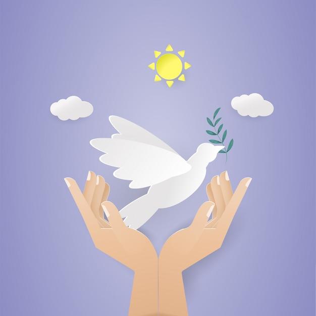 Hand, die weißen vogel mit blatt im himmel hält