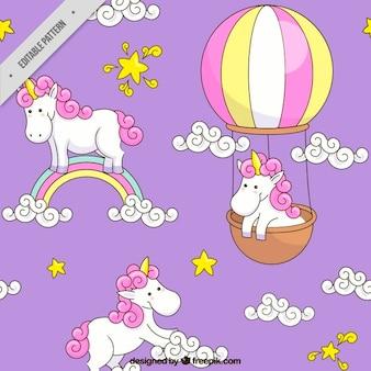 Hand gezeichnet einhorn mit regenbogen und ballonmuster