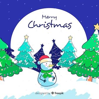 Hand gezeichneter weihnachtshintergrund und -schneemann draußen