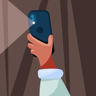 Hand hält das telefon und leuchtet eine taschenlampe