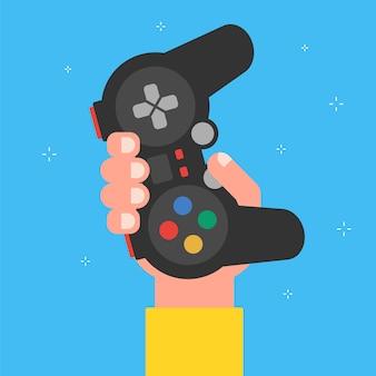Hand hält ein gamepad auf einem blauen. flache darstellung.