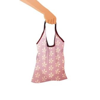 Hand hält eine baumwoll-einkaufstasche mit lebensmitteln