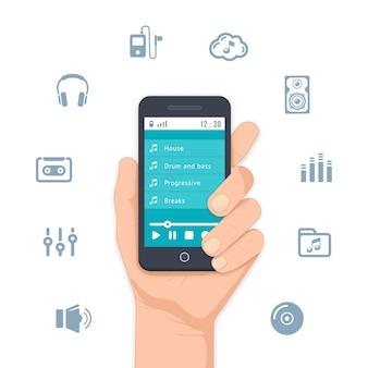 Hand hält einen mobilen mp3-player mit einer liste von musikstücken auf dem display und ist von verschiedenen musik- und unterhaltungsmöglichkeiten umgeben