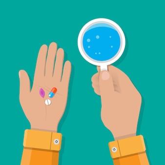 Hand hält glas wasser und pillen