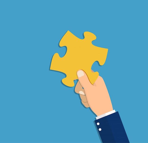 Hand hält puzzleteil