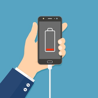 Hand hält smartphone mit angeschlossenem ladegerät und schwachem akku