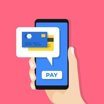 Hand hält smartphone mit kreditkarte auf dem bildschirm.
