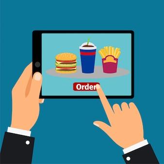 Hand hält tablette und bestellen fast food,