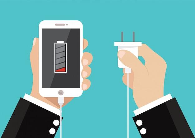 Hand halten sie smartphone und laden sie batterie und stecker auf.
