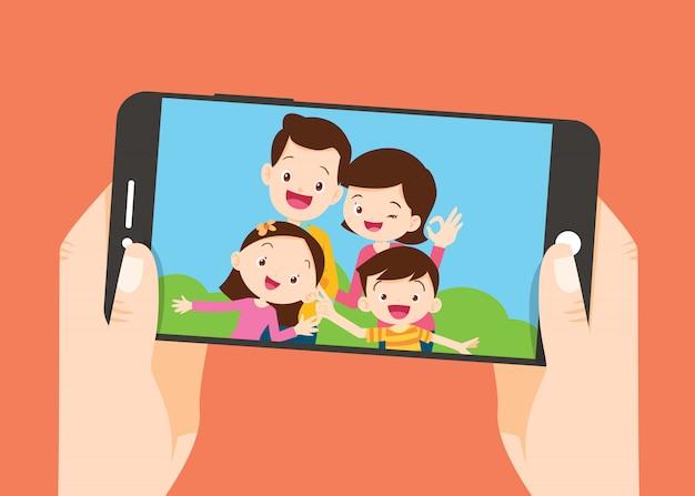 Hand halten smartphone mit der familie foto machen