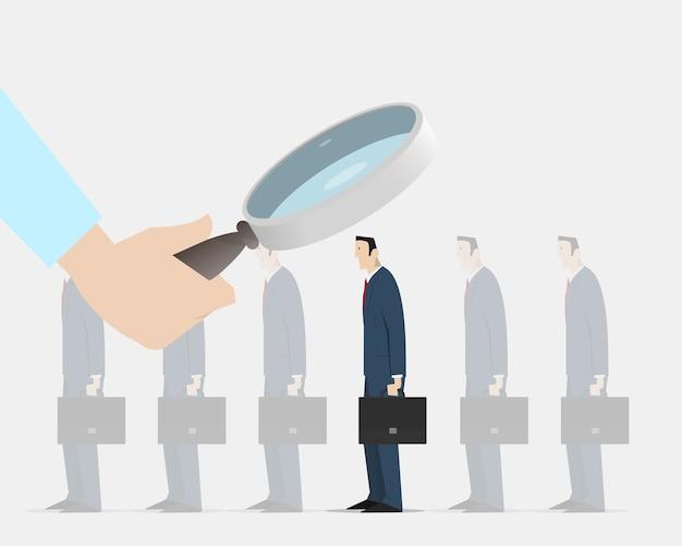Hand mit lupe zur auswahl der richtigen person aus einer gruppe identischer kollegen
