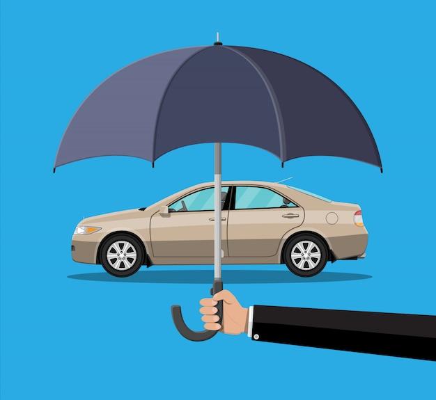 Hand mit regenschirm, der das auto schützt.