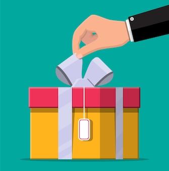 Hand öffnet geschenkbox, auspacken, auspacken.