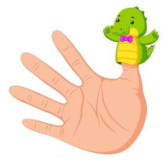 Hand trägt eine krokodilfingerpuppe am daumen