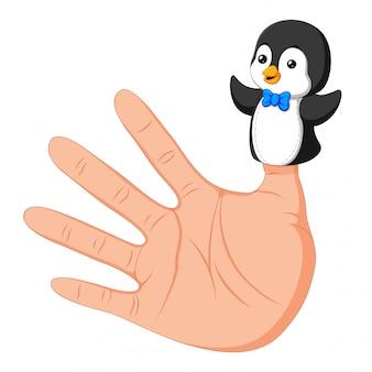 Hand trägt eine niedliche pinguin-fingerpuppe am daumen