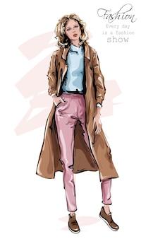 Handgezeichnete schöne junge frau im mantel stilvoller frauenlook