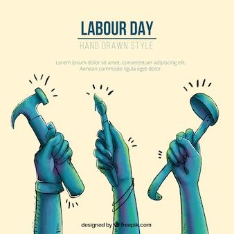 Handgezeichneter hintergrund mit händen und werkzeugen für arbeitstag