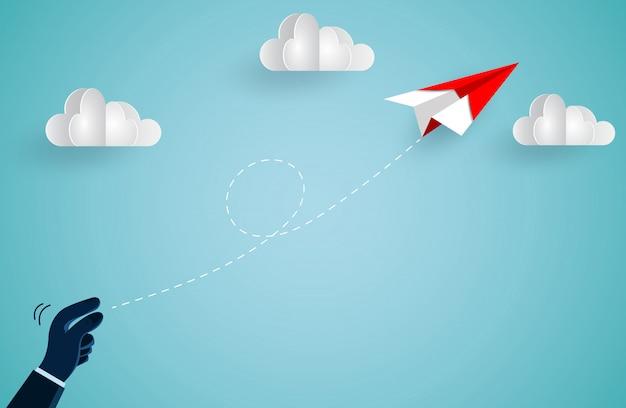 Handmensch, der das rote papierflugzeug in den himmel warf, während er über eine wolke flog