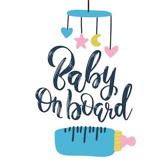 Handschriftliche phrase baby an bord mit nippel und kinder mobile. handgezeichnete inspirierende pinsel schriftzug.