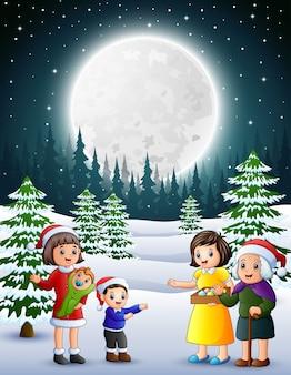 Happy familly im verschneiten garten bei nacht