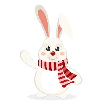 Hase in einem schal, der seine pfote auf einem weißen hintergrund winkt. weihnachtsfigur