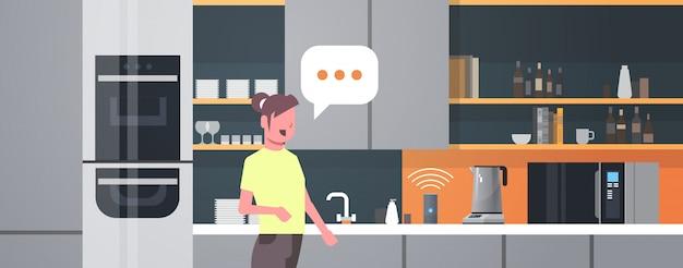 Hausfrau mit intelligenten lautsprecher spracherkennung aktiviert digitale assistenten automatisiert befehlsbericht konzept moderne küche interieur flach horizontales porträt