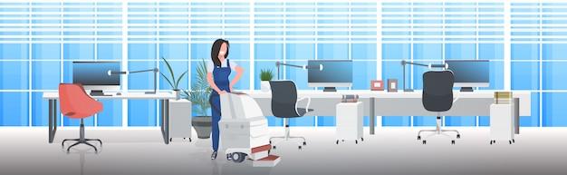 Hausmeisterin mit staubsauger lächelnde frau in uniform bodenpflege reinigungsservice konzept modernen büro interieur horizontal in voller länge