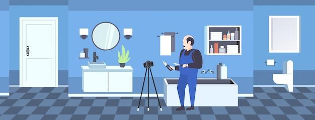 Heimwerkerarbeitskraft mit dem schraubenzieher- und ausschnittzangenblogger, der on-line-video mit digitalkamera auf blogging konzept des stativsozialen netzes modernem badezimmerinnenraum in voller länge horizontal notiert