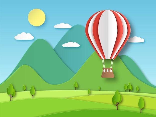 Heißluftballonpapier. roter fliegender ballon der origami-kunst auf hintergrund des berges und der bäume