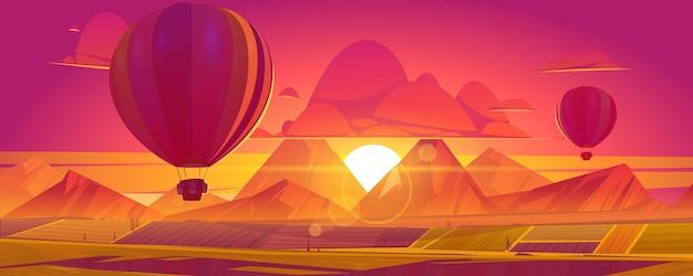 Heißluftballons fliegen über felder, berge in rotem und orangefarbenem himmel auf sonnenuntergangs- oder sonnenaufgangslandschaftslandschaft