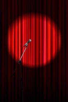 Heller roter vorhang mit mikrofon in der runden scheinwerferbeleuchtung, vertikaler hintergrund der retro-theaterbühne