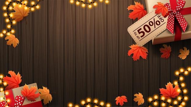 Herbstbanner mit brauner holzwand, girlandenrahmen, herbstblättern und geschenkbox, draufsicht