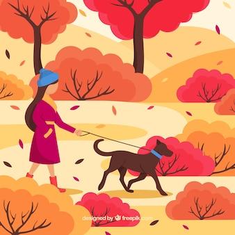 Herbsthintergrund mit der frau, die einen spaziergang mit hund macht