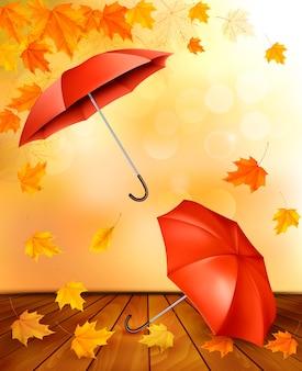Herbsthintergrund mit herbstlaub und orangefarbenen regenschirmen.