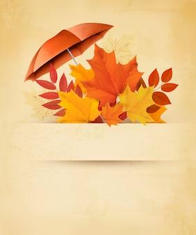 Herbsthintergrund mit herbstlaub und rotem regenschirm.
