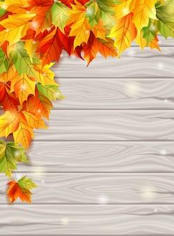Herbstlaub auf dem hintergrund des hellen hintergrundes der hölzernen bretter