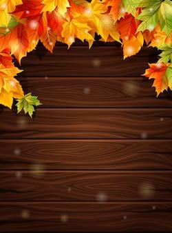 Herbstlaub gegen den dunklen hintergrund der hölzernen bretter