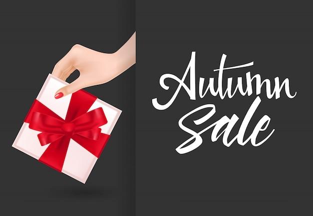 Herbstverkaufsbeschriftung mit der hand, die geschenkbox hält
