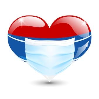 Herz in den serbischen flaggenfarben mit einer medizinischen maske zum schutz vor coronavirus