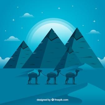 Hintergrund der ägypten-pyramiden-nachtlandschaft mit wohnwagen von kamelen
