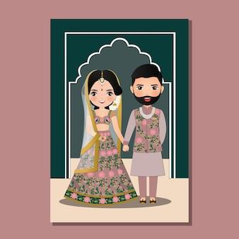Hochzeitseinladungskarte das niedliche paar der braut und des bräutigams in der traditionellen indischen kleidkarikaturcharakterillustration