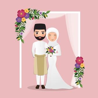 Hochzeitseinladungskarte der niedlichen malaysischen paarkarikatur der braut und des bräutigams unter dem torbogen verziert mit blumen