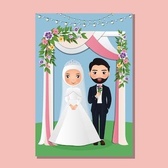 Hochzeitseinladungskarte der niedlichen muslimischen paarkarikatur der braut und des bräutigams unter dem torbogen, der mit blumen verziert wird