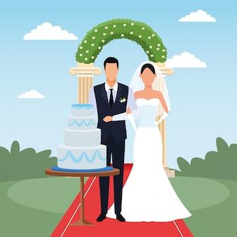 Hochzeitslandschaft mit gerade verheiratetem paar mit hochzeitstorte und blumenbogen