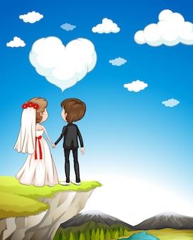 Hochzeitspaare, die auf klippe stehen