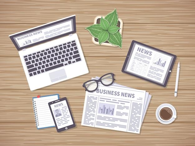 Holztisch mit täglichen nachrichten auf zeitung, tablet, laptop und telefon. überschriften, fotos, artikel auf den bildschirmen. viele möglichkeiten, um die neuesten nachrichten zu erhalten. draufsicht.